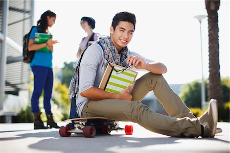 Student sitting on skateboard outdoors Stock Photo - Premium Royalty-Free, Code: 635-05971540