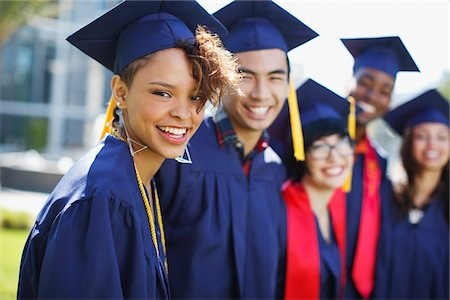 Smiling graduates standing together outdoors Stock Photo - Premium Royalty-Free, Code: 635-05971542
