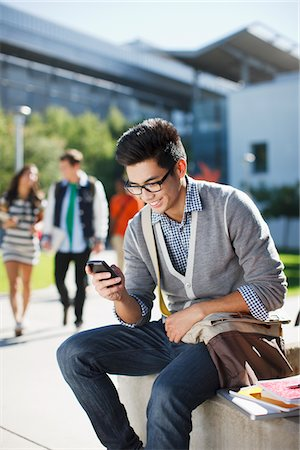 Smiling student using cell phone outdoors Stock Photo - Premium Royalty-Free, Code: 635-05971543