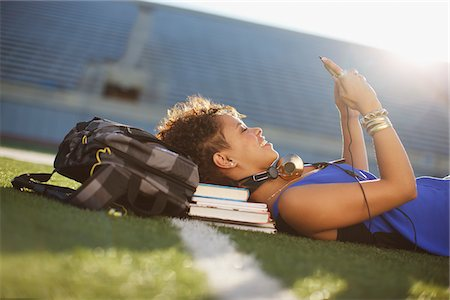 Student listening to mp3 player in grass Stock Photo - Premium Royalty-Free, Code: 635-05971555