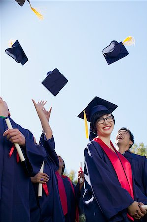 Graduates tossing caps in air outdoors Stock Photo - Premium Royalty-Free, Code: 635-05971565