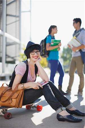 Smiling student sitting on skateboard Stock Photo - Premium Royalty-Free, Code: 635-05971569