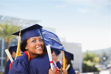 Smiling graduates hugging outdoors Stock Photo - Premium Royalty-Free, Code: 635-05971574