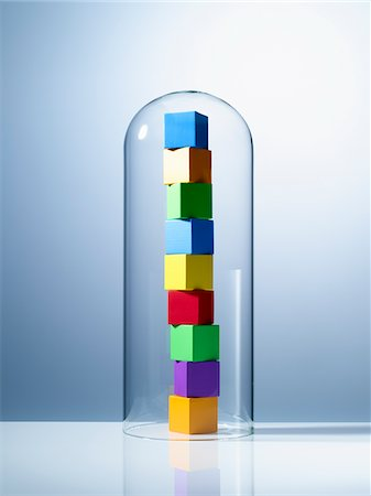 Stack of colorful cubes under glass jar Stock Photo - Premium Royalty-Free, Code: 635-05971583