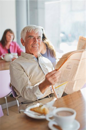 Man reading newspaper in cafe Stock Photo - Premium Royalty-Free, Code: 635-05971700