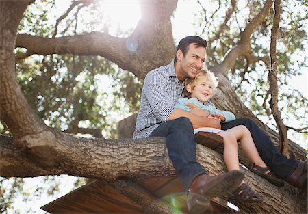 Father and son hugging in tree Stock Photo - Premium Royalty-Free, Code: 635-05971754