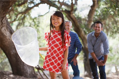 Smiling girl playing with butterfly net Stock Photo - Premium Royalty-Free, Code: 635-05971750
