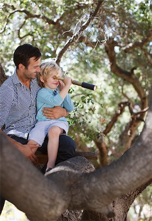 Father and son playing with telescope in tree Stock Photo - Premium Royalty-Free, Code: 635-05971785