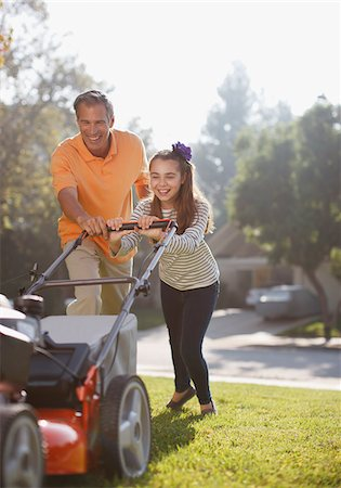 Father and daughter mowing lawn together Stock Photo - Premium Royalty-Free, Code: 635-05971794