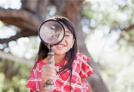 Girl using magnifying glass outdoors Stock Photo - Premium Royalty-Free, Code: 635-05971825