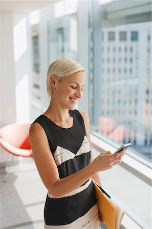 Businesswoman using cell phone in office Stock Photo - Premium Royalty-Free, Code: 635-05971879
