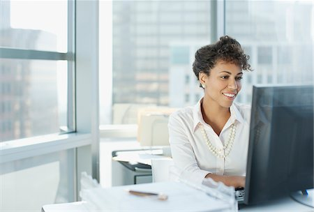 Businesswoman working at desk in office Stock Photo - Premium Royalty-Free, Code: 635-05971909