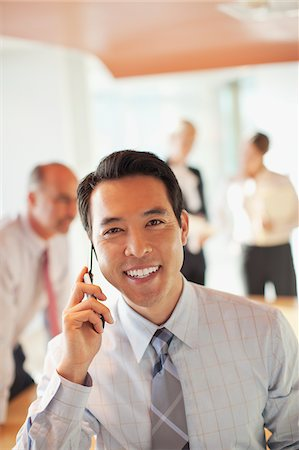 Businessman talking on cell phone in office Stock Photo - Premium Royalty-Free, Code: 635-05971937