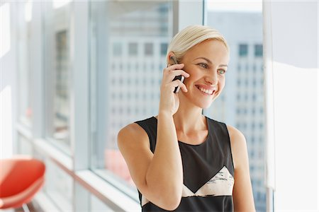 Businesswoman talking on cell phone in office Stock Photo - Premium Royalty-Free, Code: 635-05971945