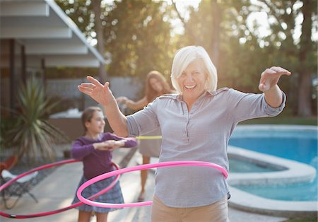 family  fun  outside - Older woman hula hooping in backyard Stock Photo - Premium Royalty-Free, Code: 635-05971962