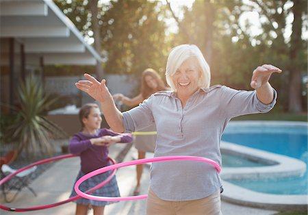 family  fun  outside - Older woman hula hooping in backyard Stock Photo - Premium Royalty-Free, Code: 635-05971962