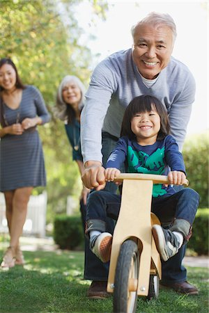 daughter middle-aged mother women young adults - Older man pushing grandson in backyard Stock Photo - Premium Royalty-Free, Code: 635-05971980