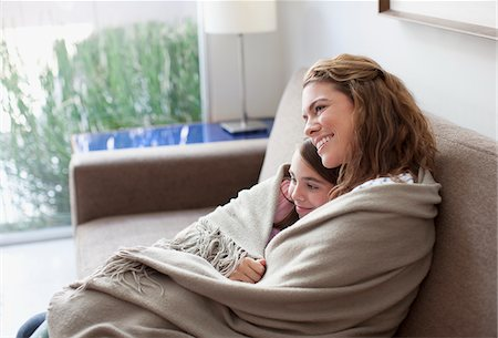 Mother and daughter wrapped in blanket on couch Stock Photo - Premium Royalty-Free, Code: 635-05971996