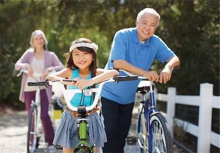 Older couple and granddaughter riding bicycles outdoors Stock Photo - Premium Royalty-Free, Code: 635-05971999