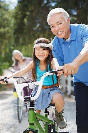 Older man helping granddaughter ride bicycle Stock Photo - Premium Royalty-Free, Code: 635-05972024