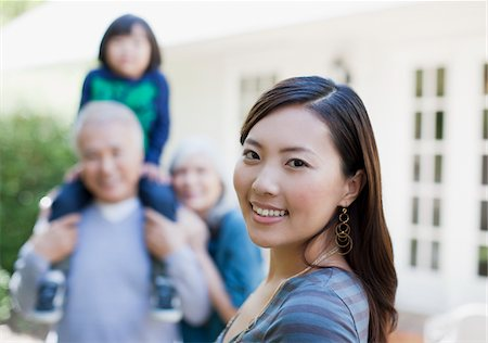 Woman smiling with family outdoors Stock Photo - Premium Royalty-Free, Code: 635-05972066