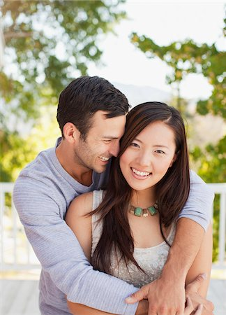 Smiling couple hugging outdoors Stock Photo - Premium Royalty-Free, Code: 635-05972079