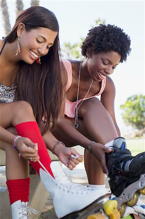 roller skate - Women lacing up roller skates outdoors Stock Photo - Premium Royalty-Free, Code: 635-05972153