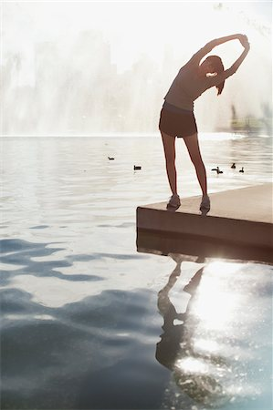 Woman stretching by still lake Stock Photo - Premium Royalty-Free, Code: 635-05972164