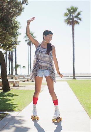 roller skate - Smiling woman skating in park Stock Photo - Premium Royalty-Free, Code: 635-05972199