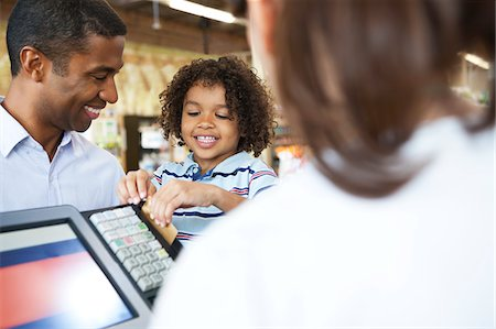 Boy running father's credit card at supermarket Stock Photo - Premium Royalty-Free, Code: 635-05972318