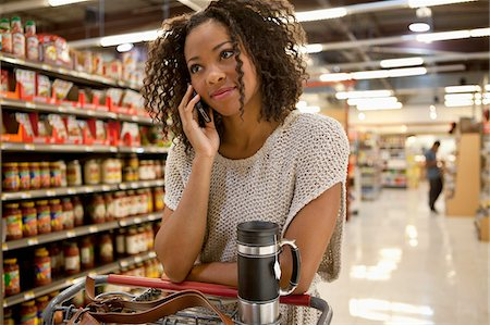Woman talking on cell phone in supermarket Stock Photo - Premium Royalty-Free, Code: 635-05972310