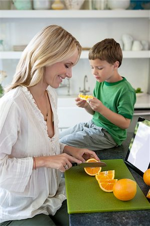 Mother slicing oranges for son Stock Photo - Premium Royalty-Free, Code: 635-05972325