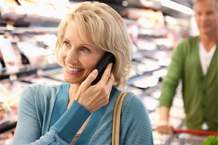 Older woman on cell phone in supermarket Stock Photo - Premium Royalty-Free, Code: 635-05972328