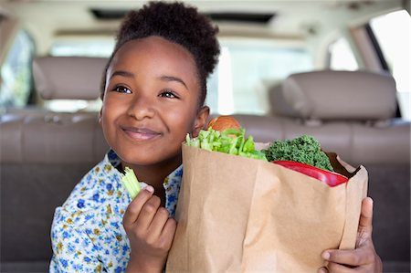 Girl eating vegetables from grocery bag Stock Photo - Premium Royalty-Free, Code: 635-05972341