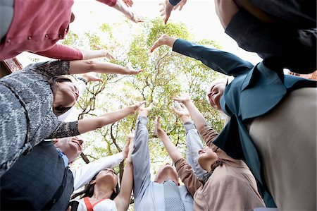 People in circle cheering together Stock Photo - Premium Royalty-Free, Code: 635-05972404