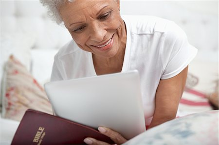 Older woman reading Bible and tablet computer Stock Photo - Premium Royalty-Free, Code: 635-05972405