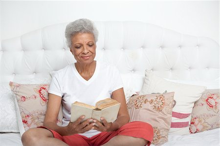 Older woman reading Bible on bed Stock Photo - Premium Royalty-Free, Code: 635-05972425