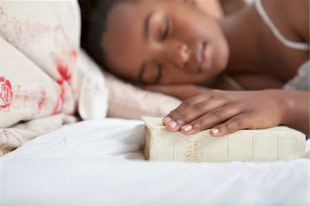 Girl asleep with Bible in bed Stock Photo - Premium Royalty-Free, Code: 635-05972420