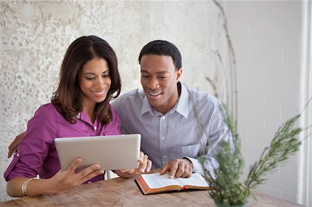Couple reading from Bible and tablet Stock Photo - Premium Royalty-Free, Code: 635-05972455