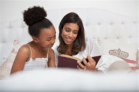 Mother and daughter reading Bible together Stock Photo - Premium Royalty-Free, Code: 635-05972462