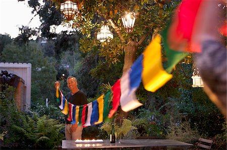 dangling - Man hanging prayer flags in backyard Stock Photo - Premium Royalty-Free, Code: 635-05972505