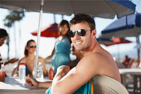 Smiling man sitting at table outdoors Stock Photo - Premium Royalty-Free, Code: 635-05972674