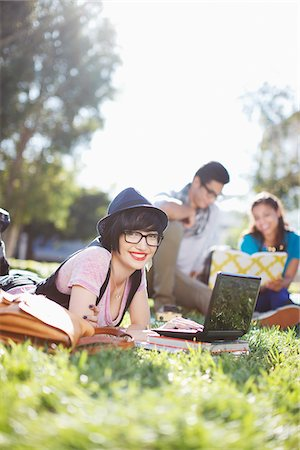 Student using laptop in grass outdoors Stock Photo - Premium Royalty-Free, Code: 635-05972698