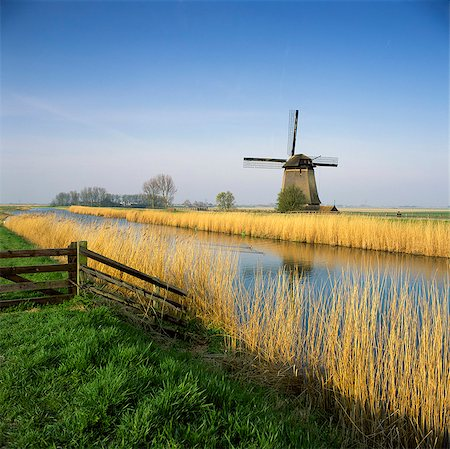 Windmill and wheatfield along rural river Stock Photo - Premium Royalty-Free, Code: 635-05972801