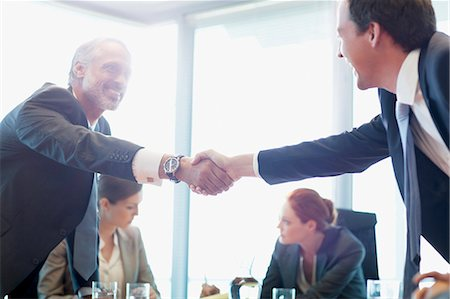 Businessmen shaking hands in conference room Stock Photo - Premium Royalty-Free, Code: 635-06045025