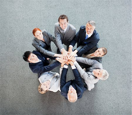 partnership - High angle view portrait of business people joining hands in circle Stock Photo - Premium Royalty-Free, Code: 635-06045033