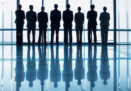 Silhouette of business people in a row looking out lobby window Stock Photo - Premium Royalty-Free, Code: 635-06045044