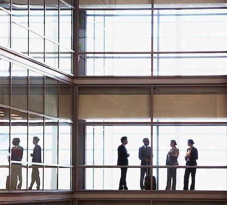 Business people talking in modern office corridor Stock Photo - Premium Royalty-Free, Code: 635-06045055
