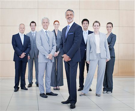 Portrait of smiling business people at bottom of escalator Stock Photo - Premium Royalty-Free, Code: 635-06045056