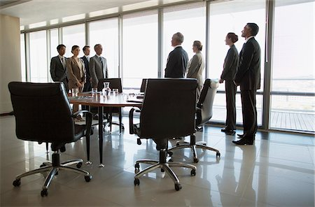Separate groups of business people facing off in conference room Stock Photo - Premium Royalty-Free, Code: 635-06045052